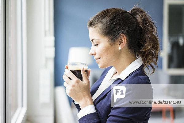 Lächelnde Geschäftsfrau genießt ein Glas Kaffee