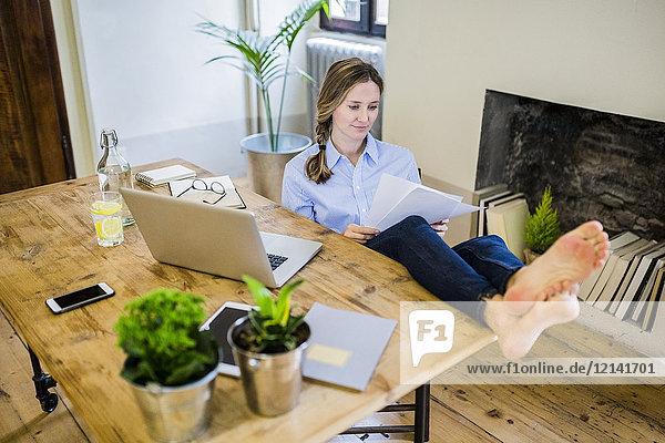 Frau sitzt zu Hause am Schreibtisch und liest mit den Füßen nach oben.
