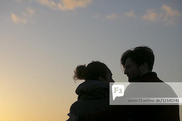 Silhouette eines jungen Paares im Freien bei Sonnenuntergang