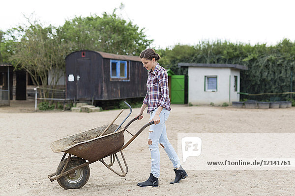 Woman walking with wheelbarrow on horse farm