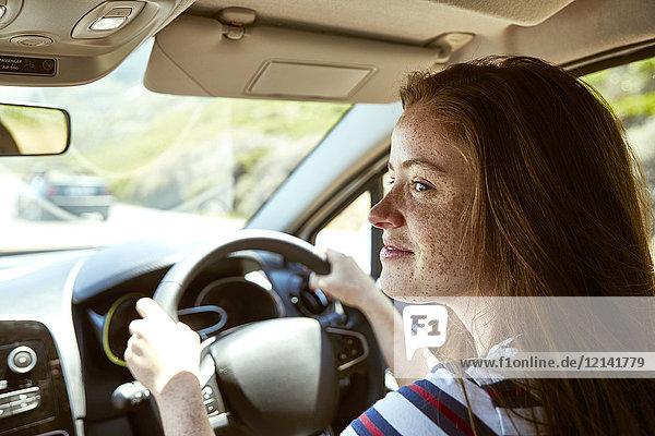 Lächelnde junge Frau mit Sommersprossen beim Autofahren  die zur Seite schaut