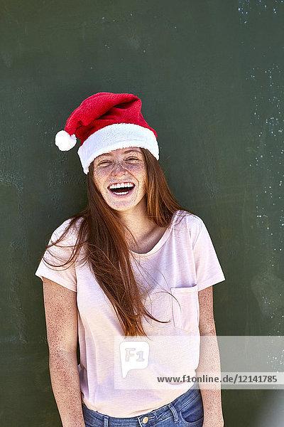 Porträt einer lachenden jungen Frau mit Weihnachtshut