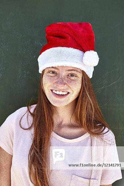 Porträt einer lächelnden jungen Frau mit Weihnachtshut