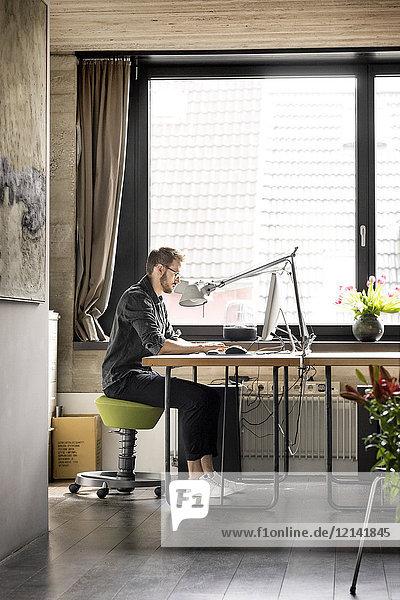 Mann arbeitet zu Hause am Schreibtisch