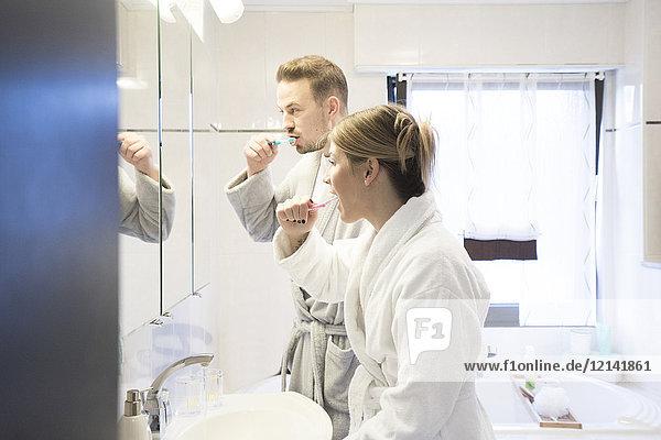 Paar beim Zähneputzen im Bad zu Hause