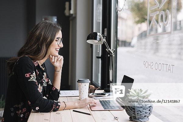 Lachende Frau bei der Arbeit am Laptop am Schreibtisch im Tattoostudio