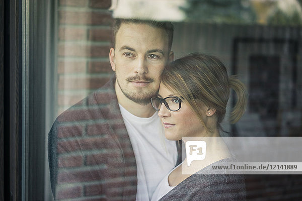 Paar zu Hause hinter der Fensterscheibe mit Blick nach draußen