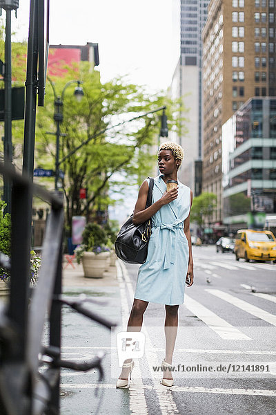 USA  New York  young blonde african-american woman with coffee mug and smart phone