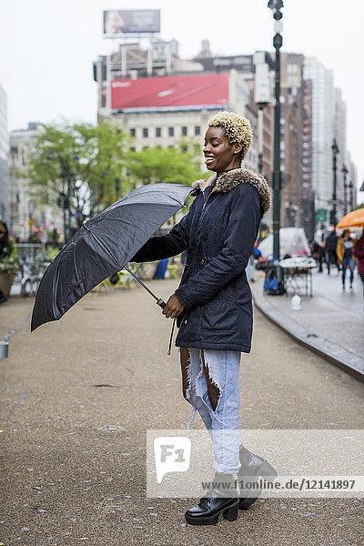 USA  New York City  Portrait einer lachenden jungen Frau mit Regenschirm