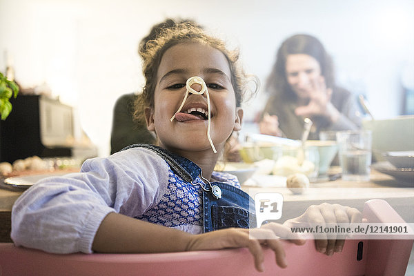 Porträt eines frechen Mädchens beim Spaghettiessen