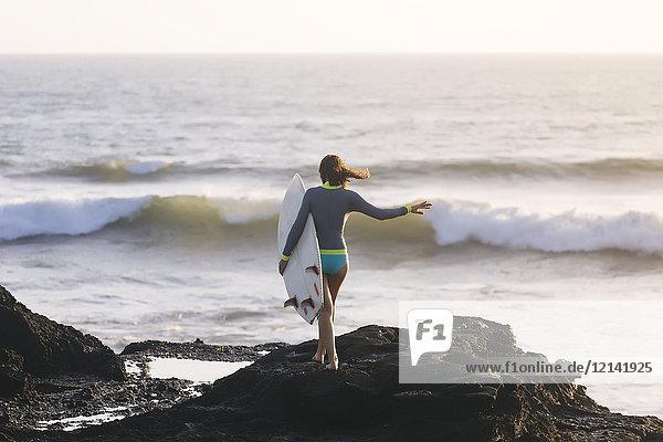 Indonesien  Bali  Junge Frau mit Surfbrett