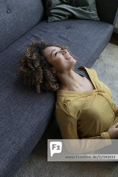 Lächelnde junge Frau  die sich zu Hause auf die Couch lehnt.