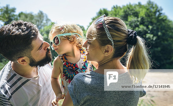 Little girl with sunglasses giving kisses to her parents