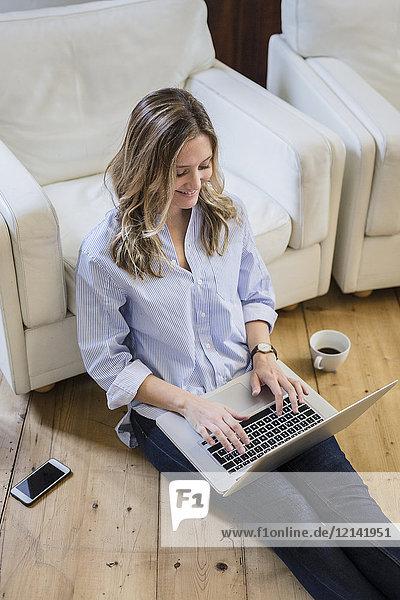 Frau sitzt zu Hause auf dem Boden und benutzt den Laptop.