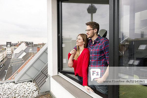 Lächelndes junges Paar schaut aus dem Fenster in der Stadtwohnung