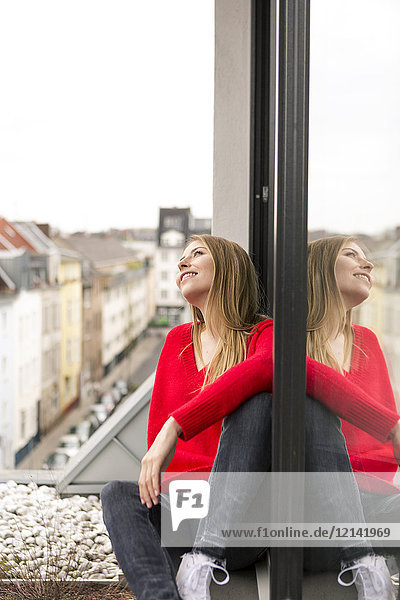 Lächelnde junge Frau sitzt am Fenster in der Stadtwohnung