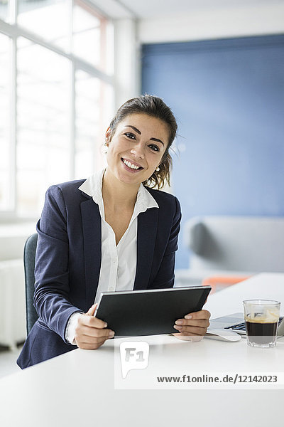 Porträt einer glücklichen Geschäftsfrau mit Tablette am Schreibtisch im Büro