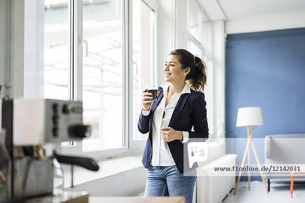 Fröhliche Geschäftsfrau mit einem Glas Kaffee in einem Loft aus dem Fenster schauend