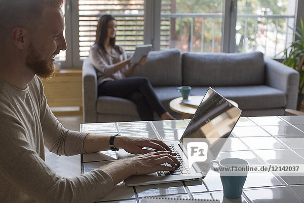 Man with laptop and woman with tablet at home