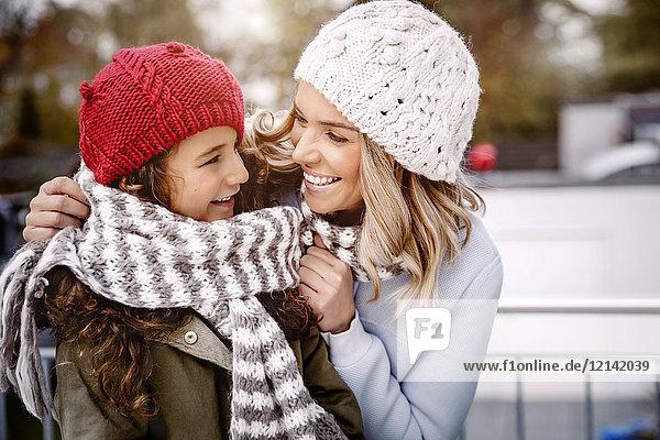 Glückliche Mutter und ihre kleine Tochter mit Wollmützen und Strickschal