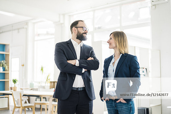 Lächelnde Geschäftsfrau und Geschäftsmann im Büro