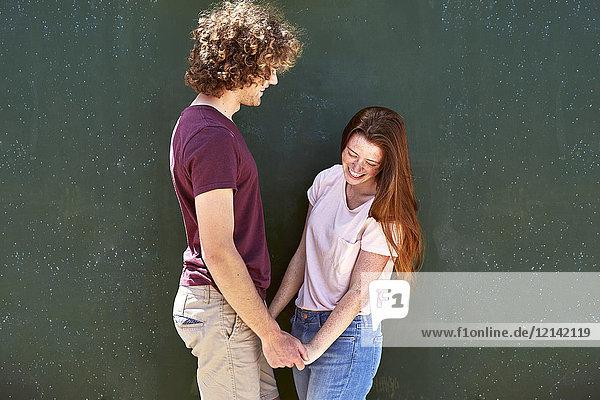 Glückliches junges Paar vor einer grünen Wand