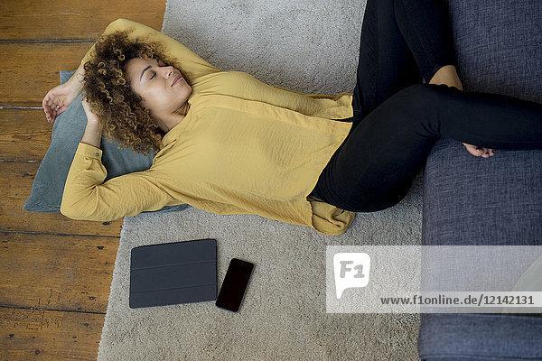 Junge Frau mit geschlossenen Augen zu Hause auf dem Boden liegend