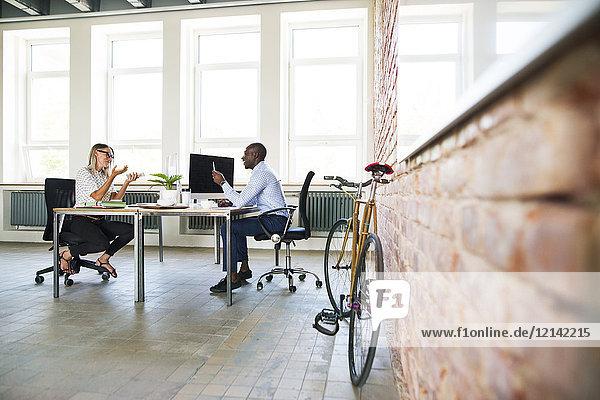 Kollegen im Start-up-Unternehmen  die im Büro sitzen und diskutieren