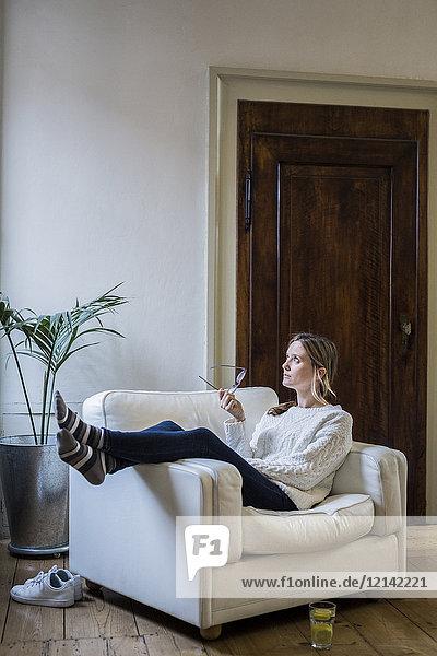 Frau sitzt zu Hause im Sessel und denkt.