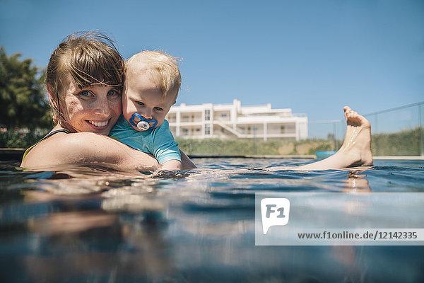 Porträt der lächelnden Mutter und des kleinen Sohnes im Schwimmbad