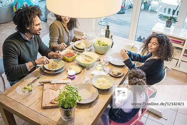 Glückliche Familie beim gemeinsamen Essen von Pizza und Pasta
