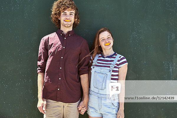 Junges Paar steht vor einer grünen Wand mit Orangenscheiben im Mund.