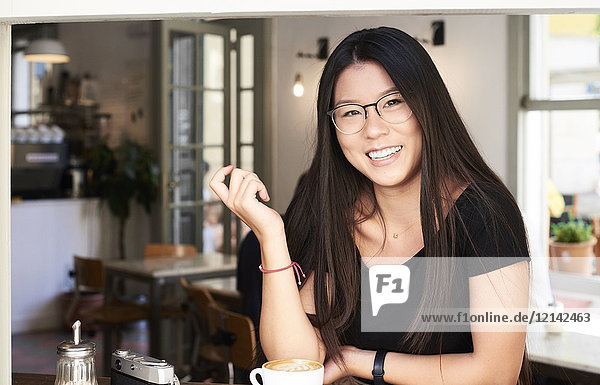 Asiatische junge Frau lächelt vor der Kamera in einem Coffee-Shop