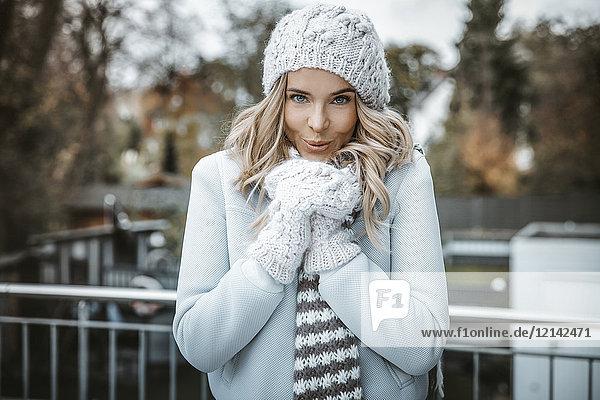 Porträt einer lächelnden Frau mit Wollmütze  Handschuhen und Schal