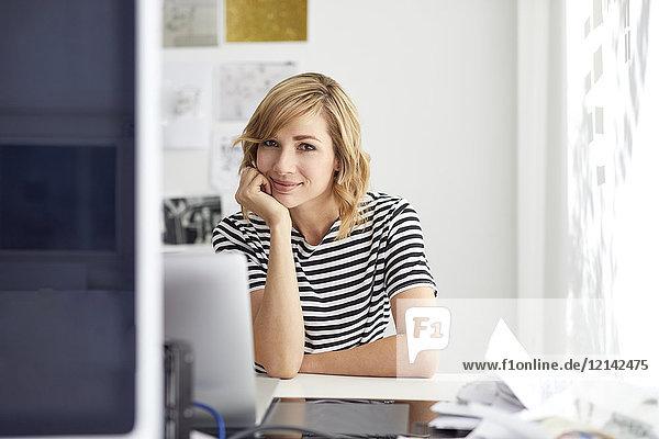 Portrait einer lächelnden blonden Geschäftsfrau mit Laptop