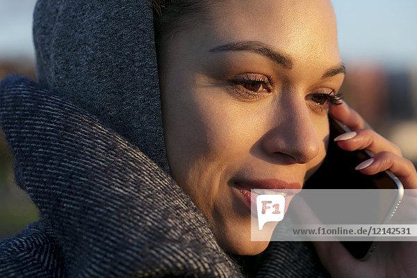 Porträt einer jungen Frau auf dem Handy im Freien