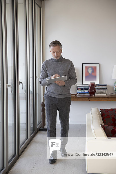 Businessman using tablet in apartment