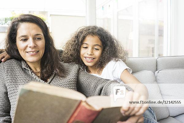 Mutter und Tochter sitzen auf der Couch und lesen ein Buch.