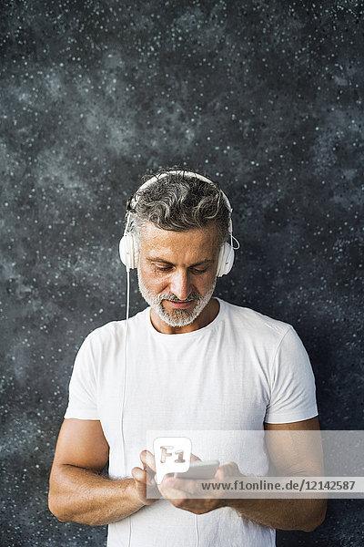 Porträt eines reifen Mannes mit Smartphone und Kopfhörern