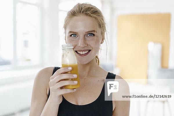Porträt einer lächelnden jungen Frau in Sportbekleidung  die einen Smoothie trinkt.