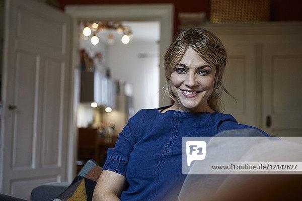 Porträt einer lächelnden Frau auf der Couch zu Hause