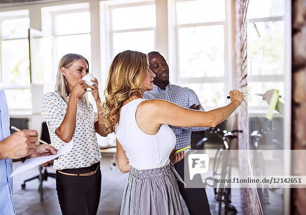 Business-Team arbeitet gemeinsam an einem Whiteboard im Büro