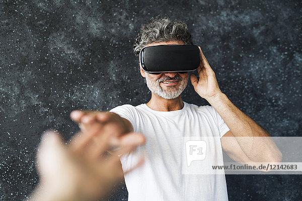 Älterer Mann mit VR-Brille  der mit den Händen ausstreckt.