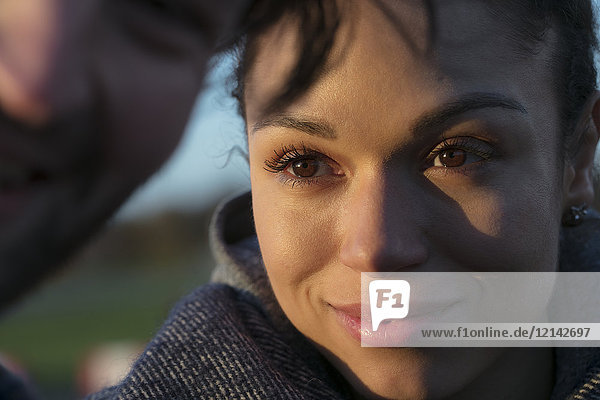 Porträt einer lächelnden jungen Frau  die ihren Freund im Freien ansieht.