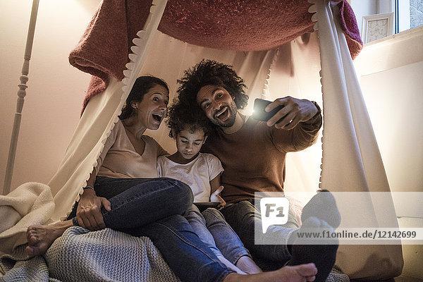 Eltern sitzen im Kinderzimmer mit Tochter  schauen auf das digitale Tablett  nehmen einen Selfie