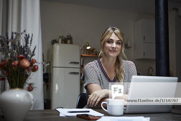 Porträt einer lächelnden Frau mit Laptop am Tisch in der Küche