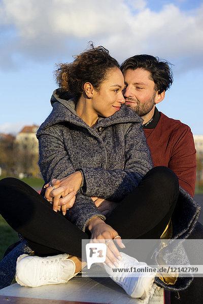 Lächelndes junges Paar im Freien sitzend