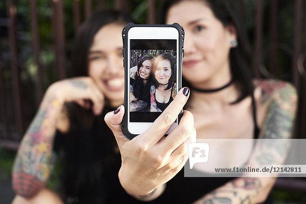 Frau hält Handy mit Selfie von sich und ihrer lesbischen Partnerin