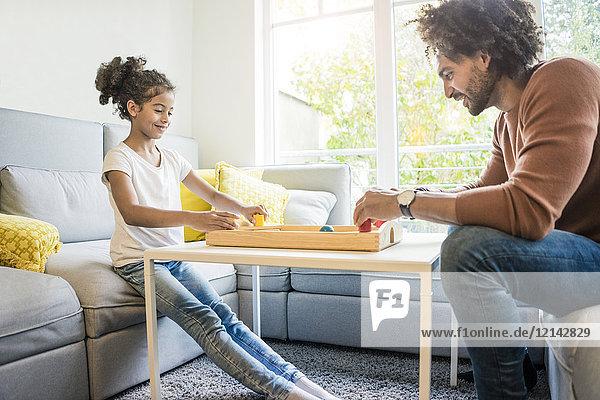 Vater und Tochter sitzen auf der Couch und spielen Tischfußball.