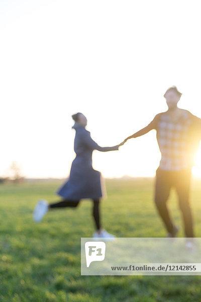Verschwommene Ansicht des Paares auf einer Wiese bei Sonnenuntergang